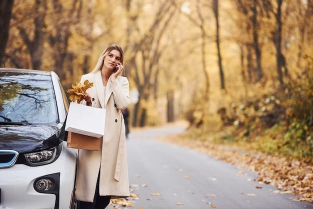 Mädchen haben einen anruf, wenn sie in der nähe des autos stehen. modernes brandneues auto im wald.