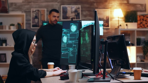 Mädchen-hacker mit brille und hoodie, während sie mit ihrem team persönliche daten stiehlt.
