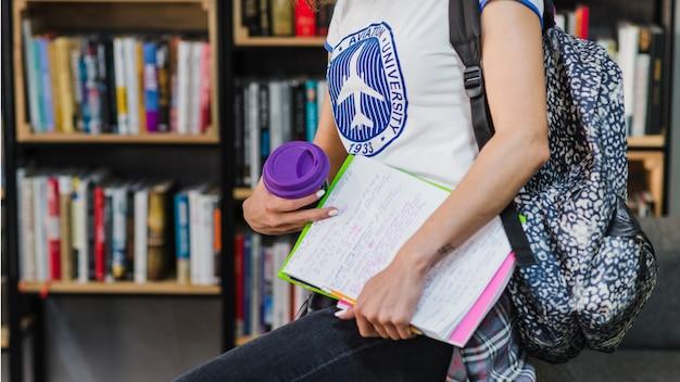 Mädchen hält arbeitsbuch mit rucksack