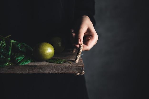 Mädchen hält auf einem vintage-tablett einen spinat mit limette. veganes, gesundes essen, öko.
