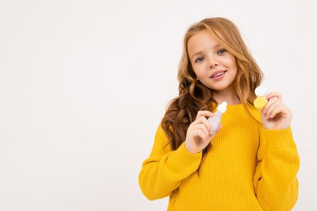 Mädchen hält augentropfen und einen behälter mit linsen