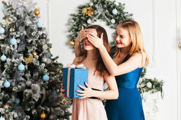 Mädchen hält die augen seiner freundin bedeckt, während sie ein geschenk gibt, überraschung für weihnachten