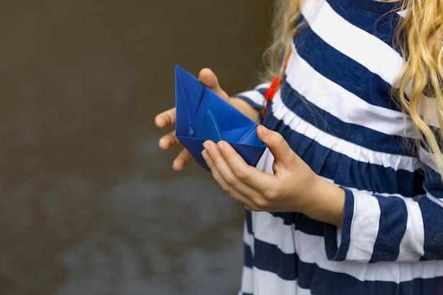 Mädchen hält ein blaues papierboot in den händen in einer pfütze nach dem regen, sommer