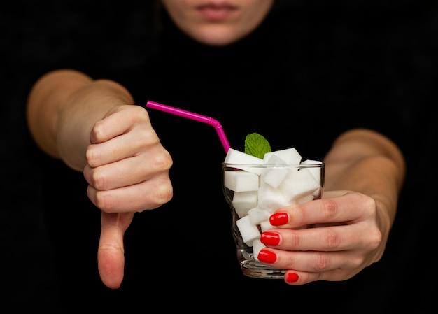 Mädchen hält ein glas gefüllt mit würfeln des weißen zuckers an, lehnt den gebrauch des zuckers ab