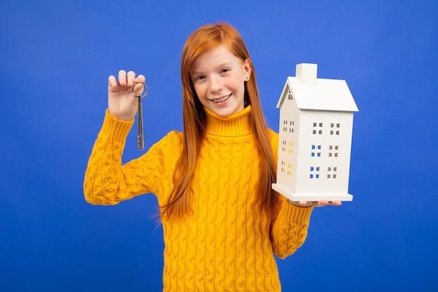 Mädchen hält ein hausmodell und türschlüssel in der hand auf blau. die eigenschaft