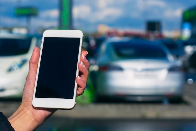 Mädchen hält ein smartphone in den händen. mock-up-telefon mit weißem bildschirm vor dem hintergrund eines elektroautos an einer ladestation.