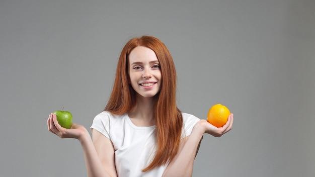 Mädchen hält eine orange und einen apfel.