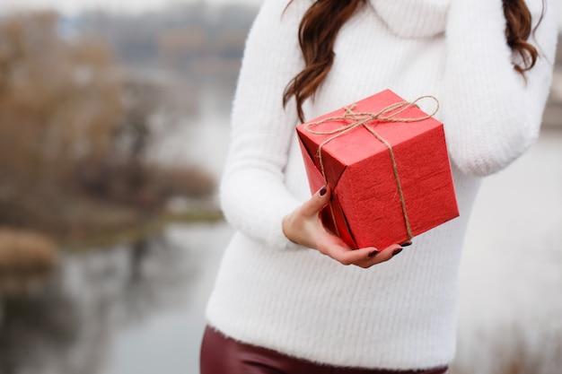 Mädchen hält eine schachtel mit einem geschenk in den händen, nahaufnahme. das konzept für den valentinstag