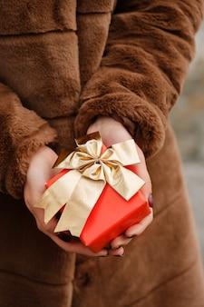 Mädchen hält eine schachtel mit einem geschenk in der hand nahaufnahme das konzept für den valentinstag
