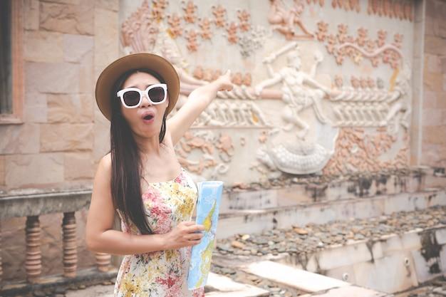 Mädchen hält eine touristische karte in der alten stadt.