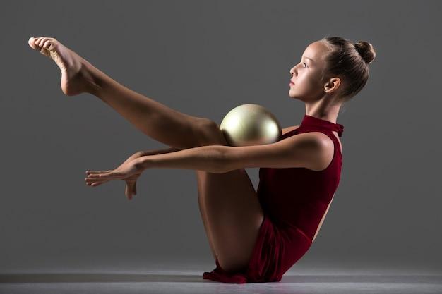 Mädchen hält einen ball mit den knien und brust