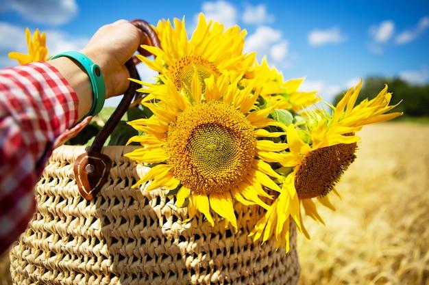 Mädchen hält einen blumenstrauß von sonnenblumen in einer strohtasche auf einem hintergrund des weizenfeldes.
