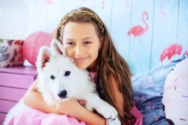 Mädchen hält einen hund im raum. das konzept von freundschaft und lebensstil.