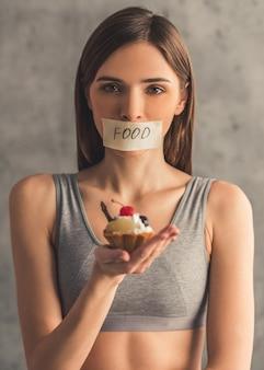 Mädchen hält einen kuchen und betrachtet kamera.