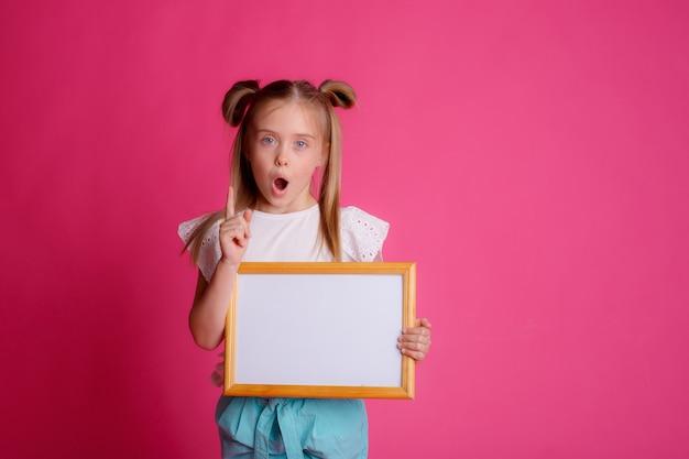 Mädchen hält einen leeren rahmen, überrascht, platz für text studio auf einem rosa