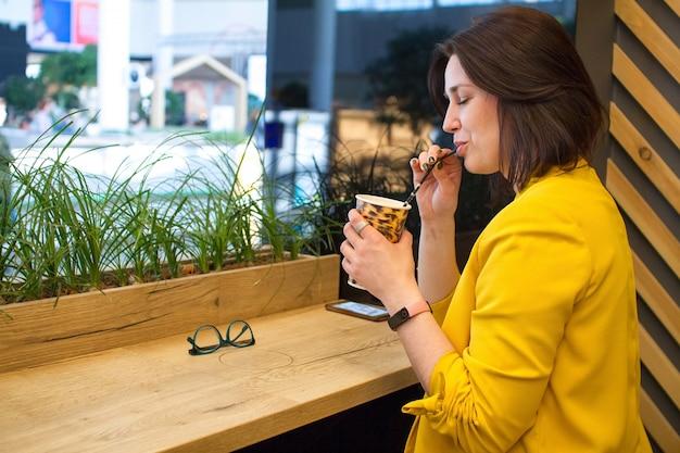 Mädchen hält einen pappbecher mit leopardenmuster und kaffee mit milch im café.