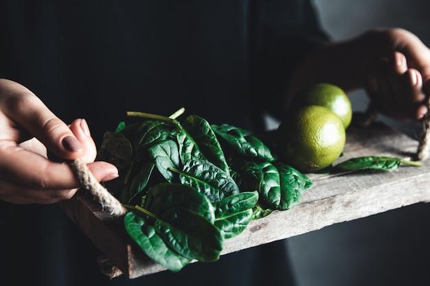 Mädchen hält einen smoothie mit spinat, avocado und limette auf einem vintage-tablett. gesundes essen, vegan, umweltfreundlich.