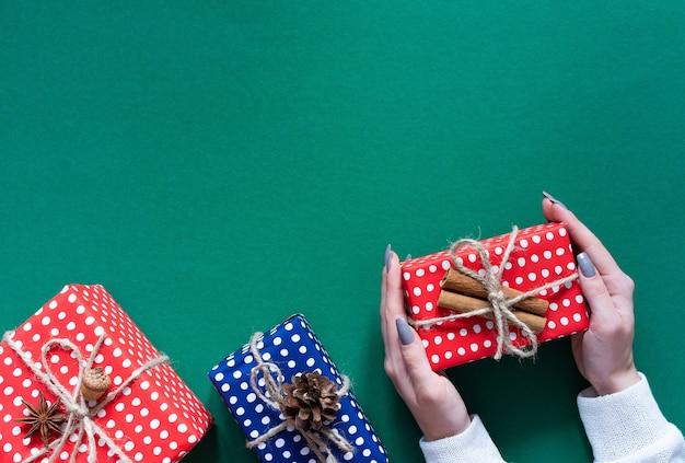 Mädchen hält geschenkbox, rote und blaue geschenkboxen in tupfen mit weihnachtsbaumkegel und eichel und zimt auf grünem hintergrund, frohe weihnachten und frohes neues jahr-konzept, flache lage, draufsicht