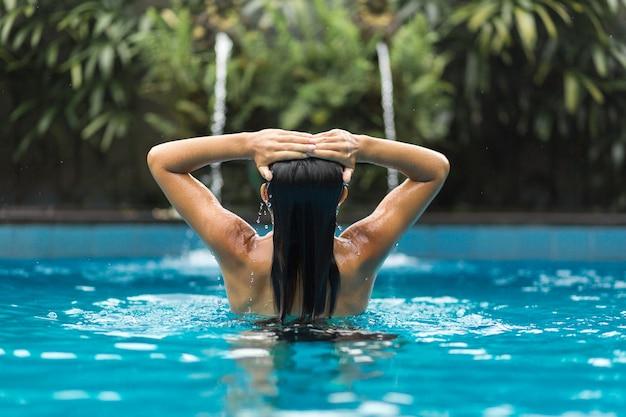 Mädchen hält ihre hände auf ihrem kopf, der im swimpool aufwirft