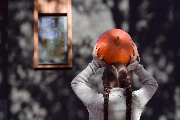 Mädchen hält im garten einen orangefarbenen kürbis unter dem kopf frisches gemüse in kinderhänden