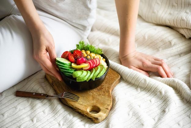 Mädchen hält in den händen vegan, rohe buddha-schüssel des detox mit avocado, quinoa, gurke, rettich, salat