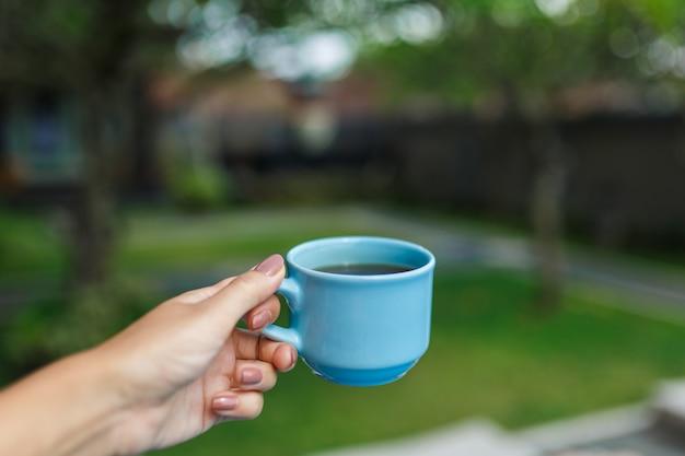 Mädchen hält in der hand eine blaue tasse mit einem getränk auf einem unscharfen grünen hof.