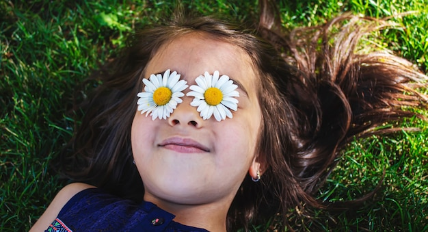 Mädchen hält kamillenblüten in ihren händen. selektiver fokus. natur.