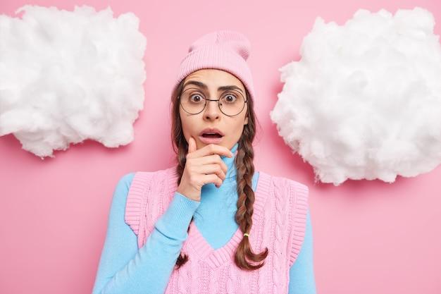 Mädchen hält kinn steht sprachlos drinnen trägt runde transparente brille freizeitkleidung reagiert auf unglaubliche nachrichtenposen gegen rosig
