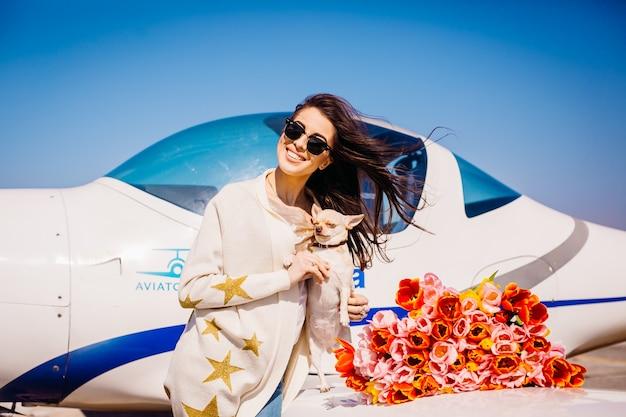 Mädchen hält kleine hundestände mit blumenstrauß von tulpen vor einem flugzeug