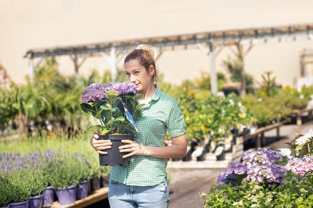 Mädchen hält lila hortensie in einem topf in einem blumenladen