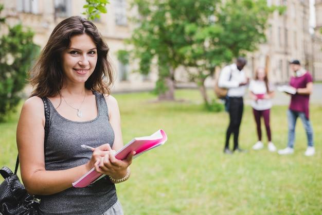 Mädchen hält notizbuch schriftlich draußen stehen