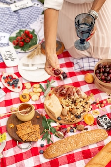 Mädchen hält saftige reife kirschen in ihrer hand auf einer karierten picknickdecke