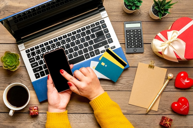 Mädchen hält smartphone, wählt geschenk, macht einkäufe, debitkarte, laptop, tasse kaffee