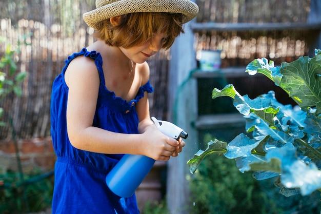 Mädchen hält sprühgerät mit pestiziden im garten