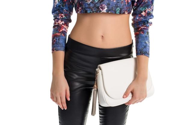 Mädchen hält weißen geldbeutel. geblümtes crop-top und hose. nagelneue lederhose. trendige kleidung und hochwertige tasche.