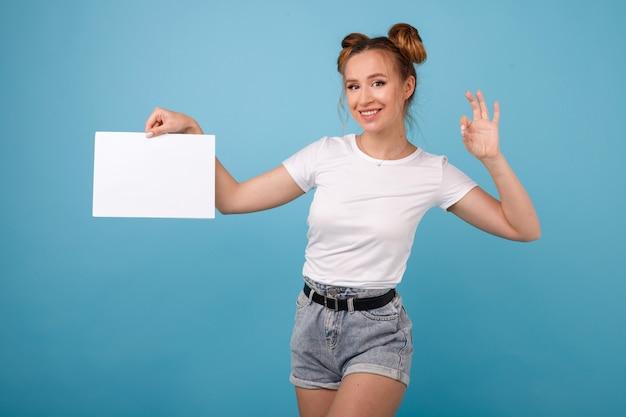 Mädchen hält weißes banner in ihren händen im raum