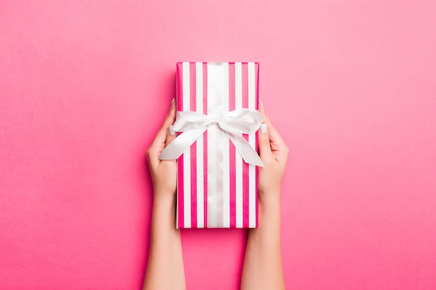 Mädchen-hände, die kraftpapiergeschenkbox auf rosa halten