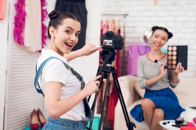 Mädchen halten bunte lidschatten mit einem mädchen hoch.