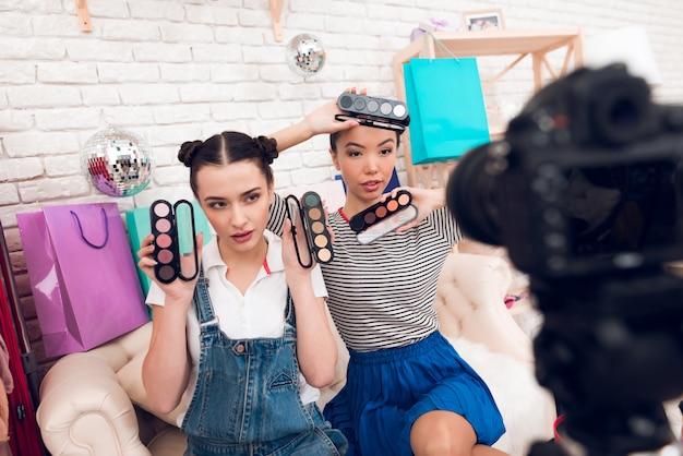 Mädchen halten bunte lidschatten zur kamera.