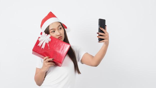 Mädchen halten geschenkbox machen selfie oder video online mit weihnachten weihnachtsstütze dekoration. asiatische thailändische jugendlich frau, die online-selfie nimmt, um festliche jahreszeit mit ihrem freund durch rote geschenkbox zu feiern. studioaufnahme.