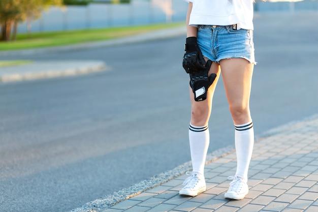 Mädchen halten spezielle handschuhe für skateboard fahren