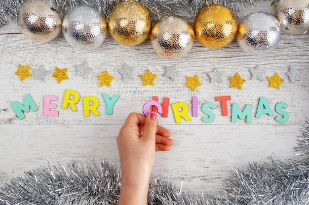 Mädchen hand, die den buchstaben c in den text der frohen weihnachten auf dem tisch mit kugeln und lametta legt