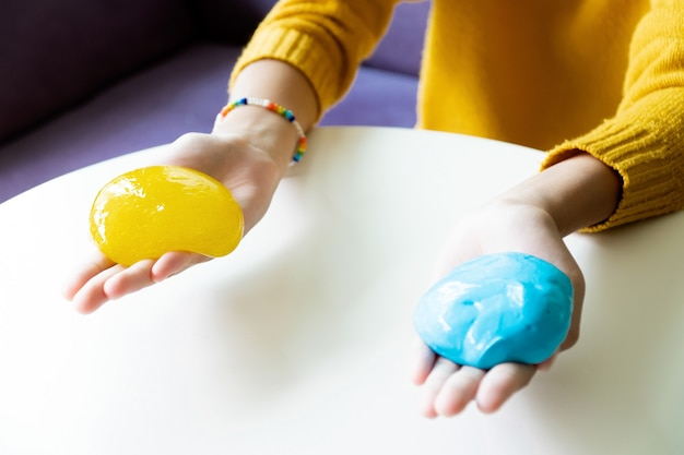 Mädchen hand hält hausgemachtes spielzeug namens schleim,
