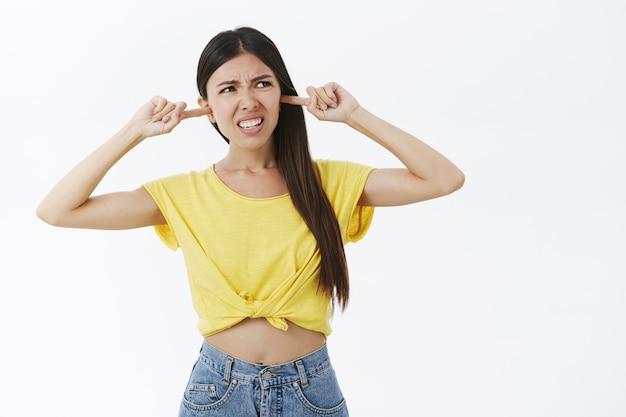 Mädchen hassen nachbarmusik, die aus flachen, schließenden ohren mit stirnrunzelnden zeigefingern und grimassen vor abneigung schreit