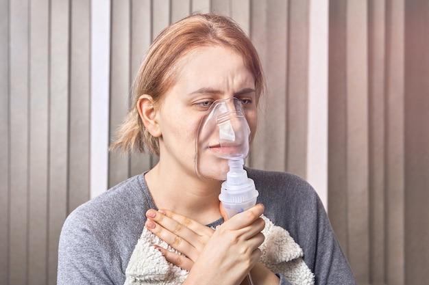 Mädchen hat einen asthmaanfall und verwendet eine verneblermaske, die zur behandlung von atemwegserkrankungen verwendet wird, um den anfall zu stoppen
