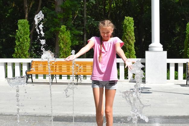 Mädchen hat spaß im straßenbrunnen