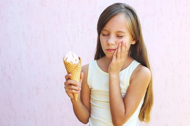 Mädchen hat zahnschmerzen von der kalten eiscreme.