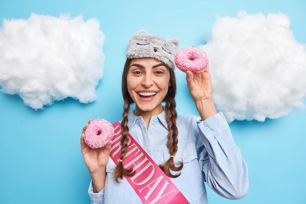 Mädchen hat zwei zöpfe hat fröhliche stimmung trägt schlafmaskenhemd lächelt angenehm posiert mit donuts genießt es, leckeres dessert zu besonderen anlässen einzeln auf blau zu essen