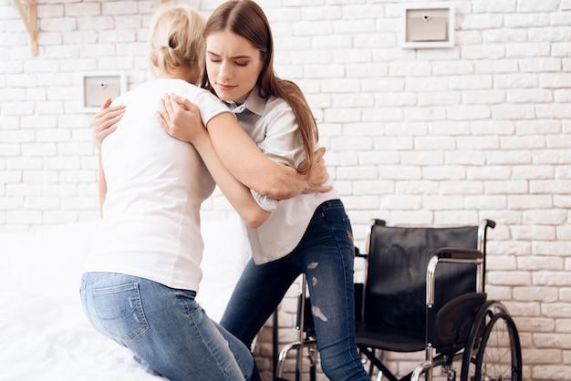 Mädchen hilft frau, in rollstuhl zu gelangen.