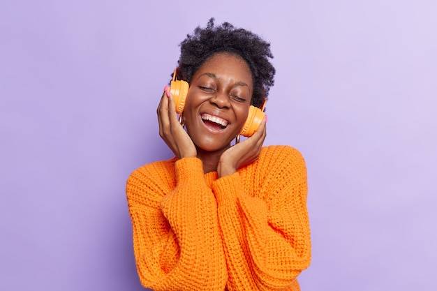 Mädchen hört musik über kabellose kopfhörer hat spaß in einem lässigen strickpullover isoliert auf lila